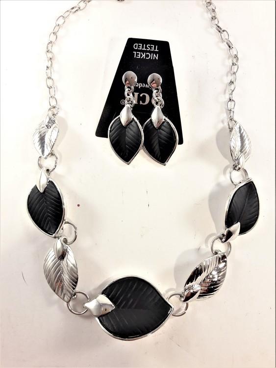 Silverfärgad halskedja med detaljer, löv i svart och silverfärg och matchande örhänge