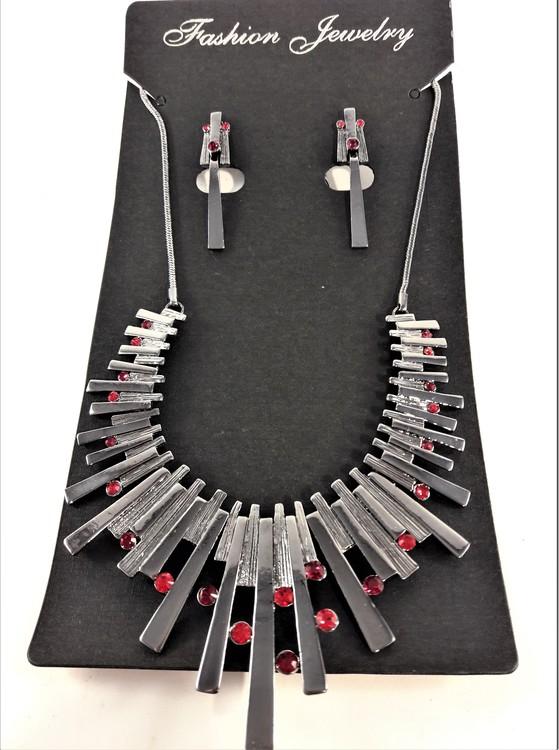 Dekorativt och vackert lyxhalsband och örhängen med vackra skimrande stenar i rött