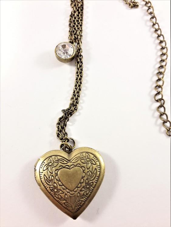 Vacker guldfärgad medaljong i kedja med glittrande sten och öppningsbart hjärta med plats för foto