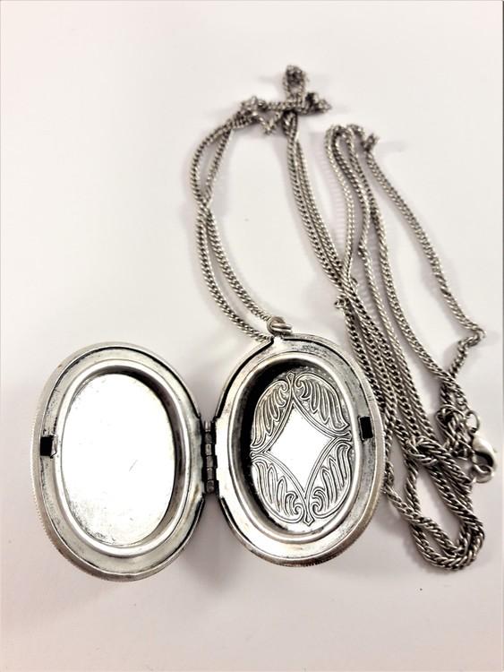 Fin silverfärgad medaljong i kedja med glittrande sten, öppningsbart med plats för foto
