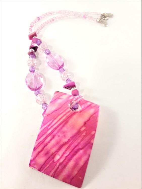 Halsband med rosa detaljer och snäckskal