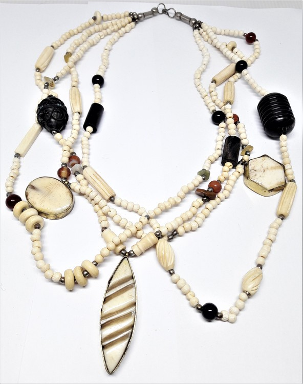 Flerradigt halsband med fina detaljer i ben, sten och metall