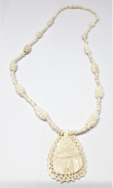 Kort halsband av ben med mindre hänge