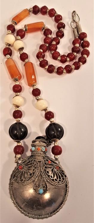 Halsband av halvädelsten med metallhänge i form av rund flaska