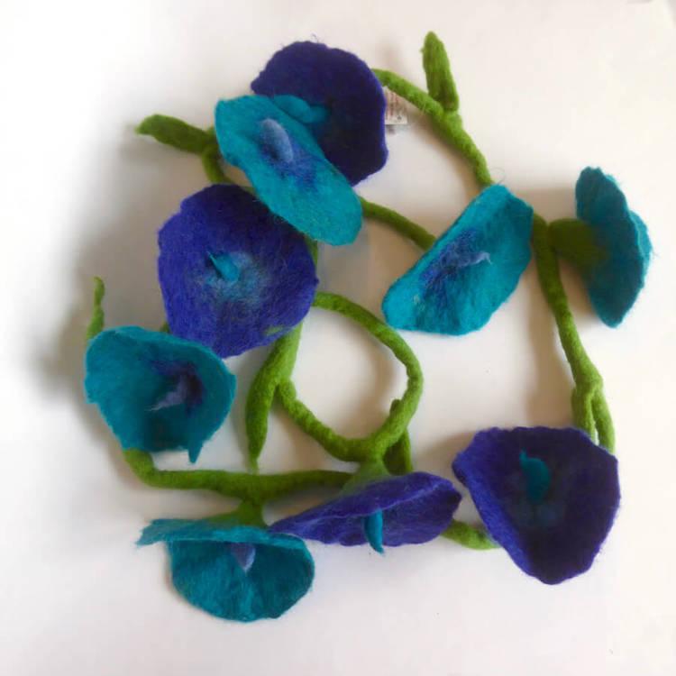 Girlang eller bordsdekoration med nio handtovade blommor, ljusblå eller djupt blå färg. 160 cm, Fair Trade från Nepal.