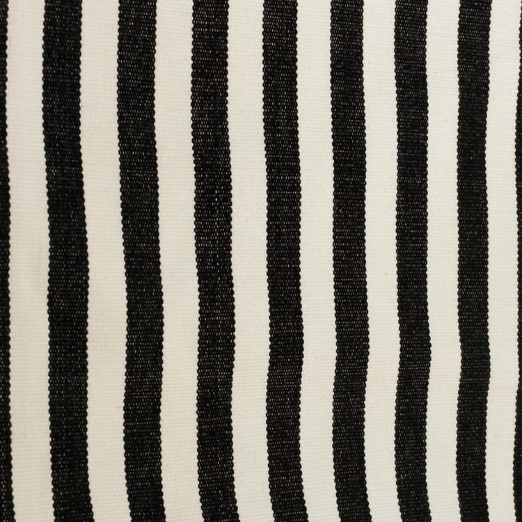 Närbild. Kuddfodral i handvävd bomull, svart och benvitt mönster.