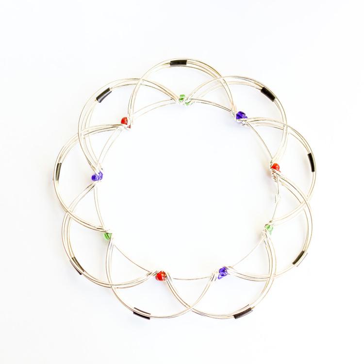 Mandalapussel i form av lotusblomma av metalltråd med glaspärlor. Hopfälld.