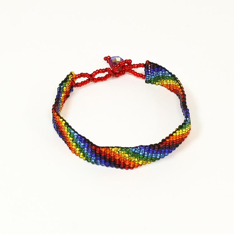 Armband i regnbågsfärger, sammansatt av mycket små glaspärlor, knäppt. Fair Trade från Guatemala.