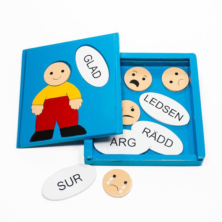 Träpussel i låda, motiv olika känslor. Ansiktsuttryck/emojis paras ihop med rätt ord: glad, ledsen, arg, sur, rädd. Öppen låda med pusselbitarna.