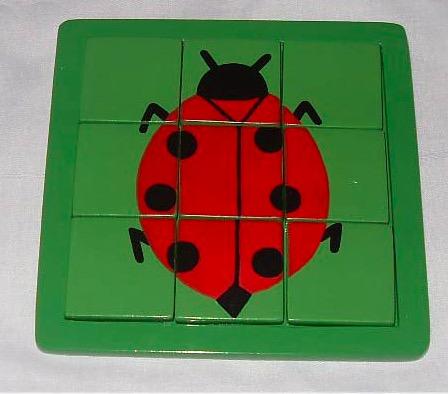 Pussel i ram, motiv nyckelpiga i nio bitar. Grön pusselplatta. Miljövänligt trä. För barn över 3 år. Fair Trade.
