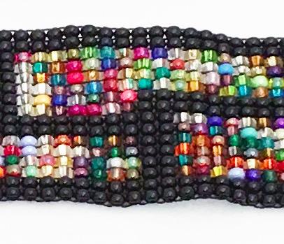 Armband av små glaspärlor. Detaljbild på det grafiska mönstret. Fair Trade.