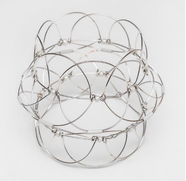 Mandalapussel i form av lotusblomma av metalltråd med vita glaspärlor.