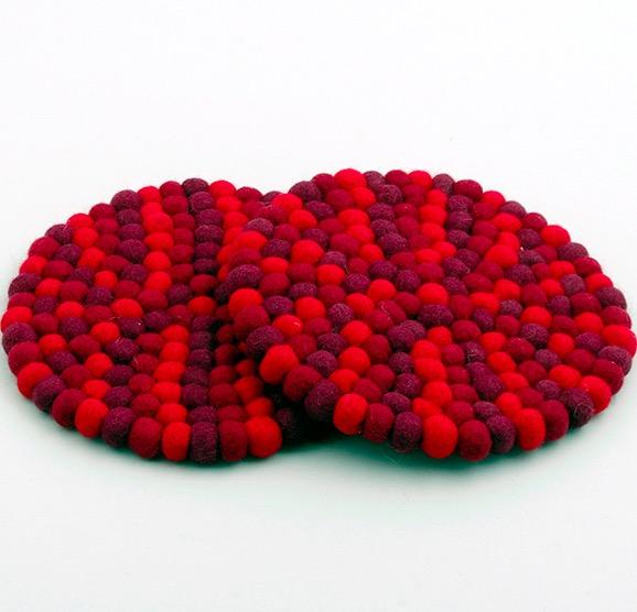 Tovat underlägg till kanna och gryta, det har sytts ihop av små bollar i röda färgnyanser. Fair Trade från Nepal.