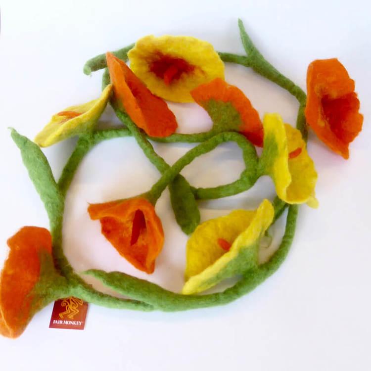 Handtovad girlang med nio blommor på en grön stjälk med små blad. Blommor i orange varvas med klargula blommor. Bordsdekoration, Fair Trade från Nepal.