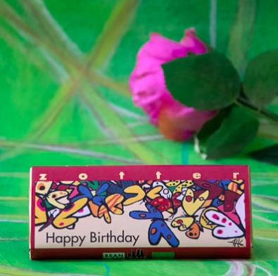Zotter Happy birthday, exklusiv mjölkchokladkaka, karamellkräm och mandelnougat. Fair Trade & ekologisk. Bild med dekoration.