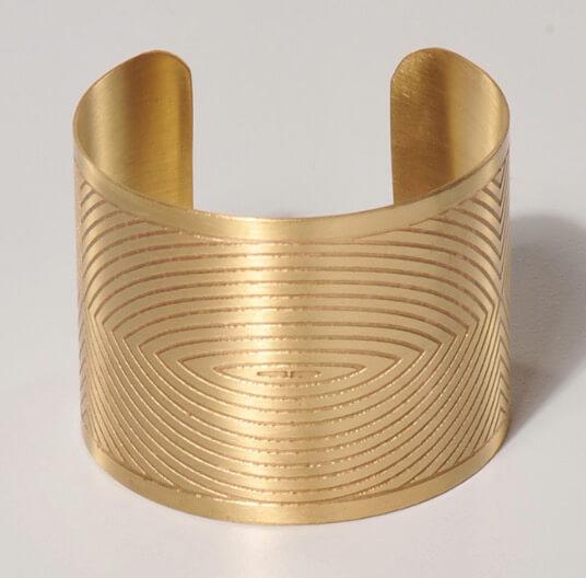 Öppen, justerba, bred  armring i guldfärgad, nickelfri mässing. Fair Trade från Indien.