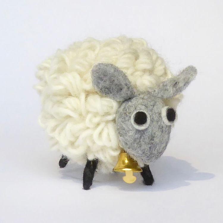 Fluffigt lockigt vitt får i ull, handgjort