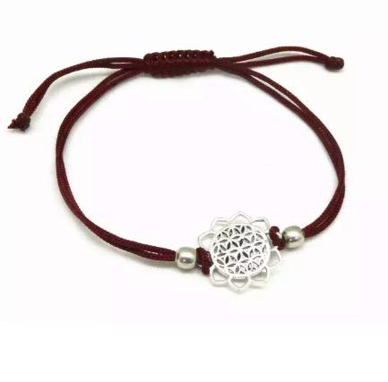 Armband med livets blomma-motiv i mässing. Justerbart band av mörkröd bomull. Fair Trade från Indien.