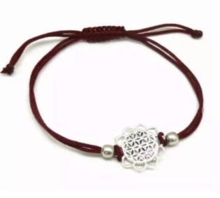 Armband i bomull, justerbart på ett snyggt sätt. Smyckets ornament är Livets blomma, silverfärgsd mässing. Fair Trade.