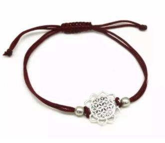 Armbasnd med justerbart bomullsband, smycket i form av Livets blomma i silverfärgad mässing. Fair Trade.