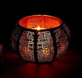 Ljuslykta, till värmeljus, järnplåt. Bågformad. Med utstansat mönster som ger fint skuggmönster. Bild i mörkret. Fair Trade.